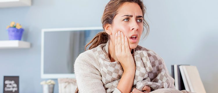woman holding her mouth due to pain caused by a tooth abscess